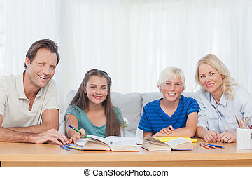 Smiling parents helping their children with their homework