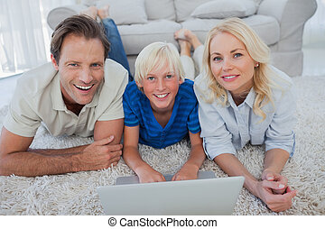 Portrait of son and parents using a laptop lying on a carpet