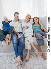 Portrait of a family watching television sitting on a couch