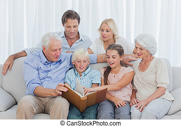 Extended family looking at a photo album in living room