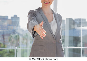Businesswoman offering hand for handshake by a large window