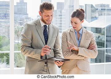Business team going over document on clipboard