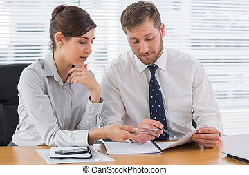 Business people going over documents at desk in office