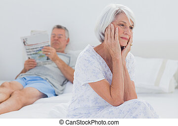 Anxious mature woman sitting on bed while husband is reading...