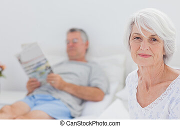 Smiling mature woman sitting in bed with husband reading a...