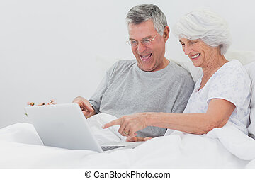 Mature man with wife pointing at a laptop in bed
