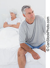 Upset man sitting on bed during a dispute with wife with...