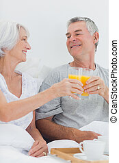 Couple clinking their orange juice glasses while having...