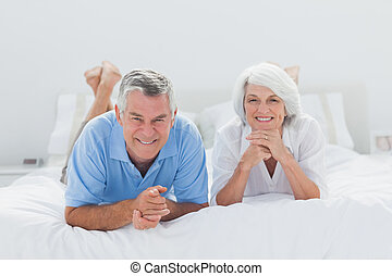 Couple lying together in bed - Mature couple lying together...