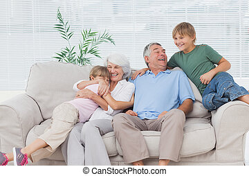 Smiling grandchildren embracing their grandparents on couch