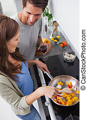 Woman cooking bell pepper while her husband is looking at...