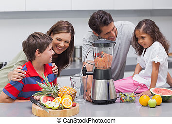 Family using a blender in the kitchen