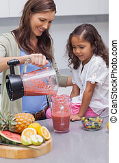 Woman pouring fruit from a blender