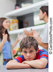 Sad little boy listening to his parents arguing in the...
