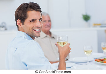 Attractive man holding a glass of white wine and looking at...