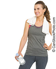 Happy fitness young woman with bottle of water looking on...
