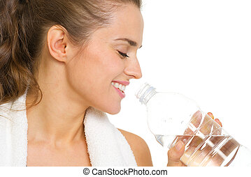 Portrait of happy young woman drinking water