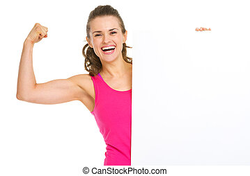 Happy fitness young woman showing biceps and blank billboard
