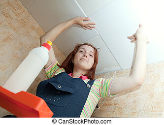 Woman glues ceiling tile at home