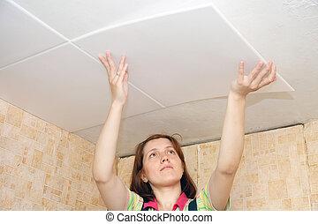 Woman glues ceiling tile - Woman glues ceiling tile at home...