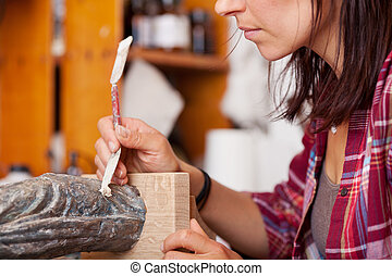 Woman Using Putty Knife On Statue - Midsection of woman...