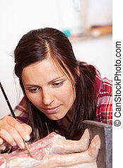 Woman Using Brush On Statue In Workshop