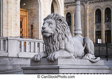 Stone lion on the background of the parliament in Oslo....