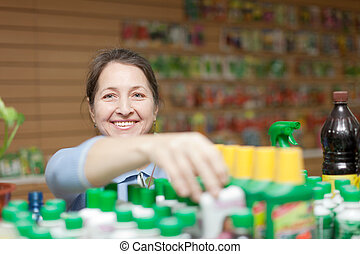 female mature gardener chooses fertilizer in bottle at store...