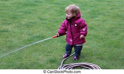 Little girl  watering grass lawn in