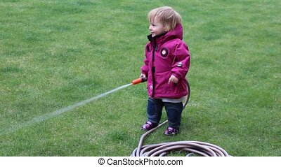 Little girl watering grass lawn in - Little girl one year...