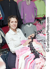 Female buyer chooses clothes in shop