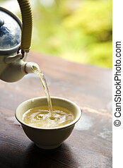 Pouring Green Tea from Pot into Cup