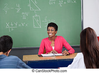 Teacher Looking Away While Sitting At Desk