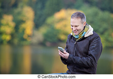 Man Using Mobile Phone Against Lake - Happy mature man using...