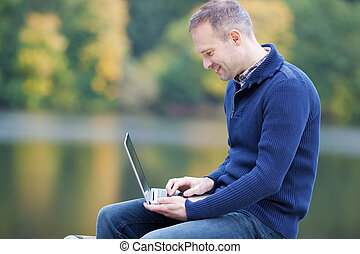 Man Using Laptop Against Lake