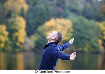 Smiling Man With Arms Outstretched Against Lake - Side view...