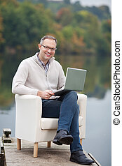 Mature Man Using Laptop While Sitting At Pier - Full length...