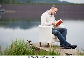 Man Reading Book While Sitting At Pier - Full length of...