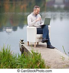 Man Using Laptop Against Lake