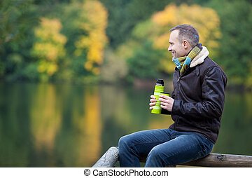Man With Thermos While Sitting On Fence