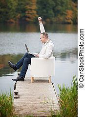 Mature Man Using Laptop While Sitting At Pier - Full side...