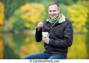 Man Dipping Tea Bag In Cup Outdoor - Happy mature man...