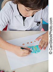 Boy Drawing With Color Pencil In Classroom - High angle view...