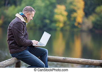 Man Using Laptop Against Lake - Happy mature man using...
