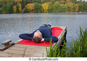 Man Lying On Pier Against Lake