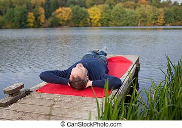 Man Lying On Pier Against Lake - Full length of mature man...