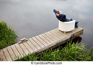 Man With Hands Behind Head Relaxing On Chair At Pier - High...