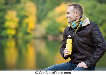 Man Holding Water Bottle While Looking Away Against Lake