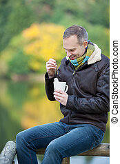 Man Dipping Tea Bag In Cup While Sitting On Fence