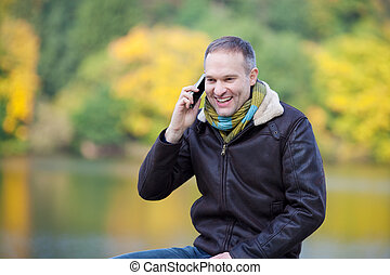 Man Using Mobile Phone While Looking Away Against Lake